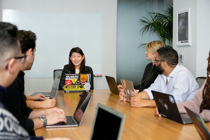 Mixed race and gender workers sitting at boardroom table.