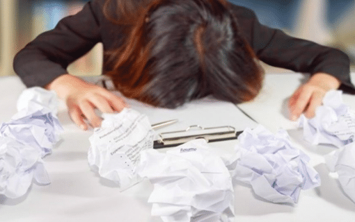 Woman head on table with scrunched up paper all around