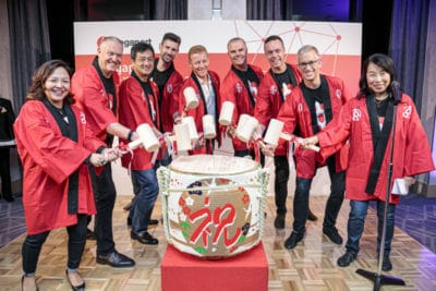 A photo of a diverse group of women and men, all wearing red jackets, pretending to bang a large Japanese drum
