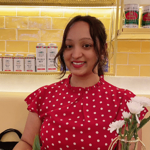 A close up photo of a smiling woman in a red polka dot top