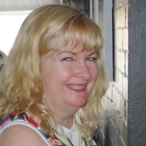 A close up photo of a woman with blonde hair, smiling