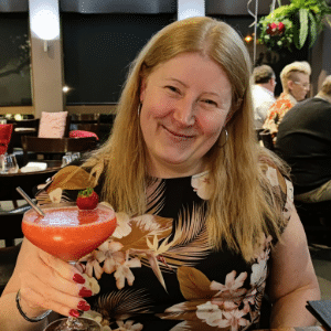 A close up photo of a woman in a restaurant, holding up a cocktail