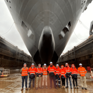 A photo of a diverse range of people, wearing high-vis jackets, standing under a ship in a dry dock