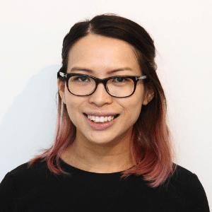 A headshot photo of a woman smiling wearing glasses