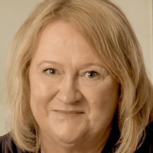 A close up photo of a white woman with blonde hair, smiling
