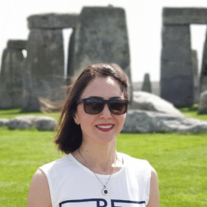 A close up photo of a smiling woman wearing sunglasses, standing in front of Stonehenge
